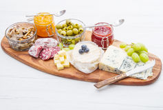 Wooden cutting board with cheese, cold cuts and jams Royalty Free Stock Images