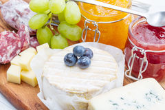 Wooden cutting board with cheese, cold cuts and jams Stock Image