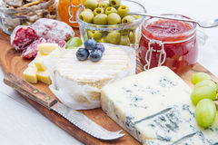 Wooden cutting board with cheese, cold cuts and jams Stock Photo