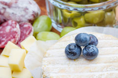 A wooden cutting board with cheese, cold cuts and jams Royalty Free Stock Images