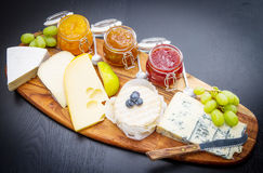 A wooden cutting board with cheese and jams Royalty Free Stock Photography