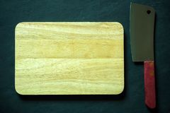 Wooden cutting board and Chinese chef knife. Wooden cutting board and Chinese chef knife on black cement floor. Top view and copy space for text. Concept of royalty free stock image