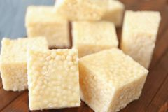 Wooden cutting board with cubes of rice treats. Closeup Stock Photos