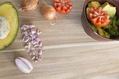 Wooden cutting board with fresh onions, tomatoes and avocado Royalty Free Stock Images