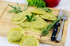 Wooden cutting board with green ravioli and vegetables royalty free stock photo