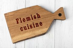 Wooden cutting board with inscription. Concept of flemish cuisine