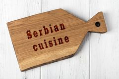 Wooden cutting board with inscription. Concept of serbian cuisine.  royalty free stock photos