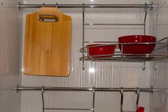 Metal shelf for dishes and a wooden cutting board from two sections. stock images