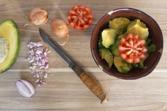 Wooden cutting board with knife, fresh onions, tomato and avocado Stock Photography