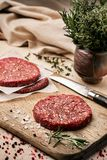 On a wooden cutting board on kraft paper there are raw beef burgers for burgers, spices, rosemary, a pepper mill, a. Cooking process. Top view. Copy space Stock Photography