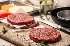 On a wooden cutting board on kraft paper there are raw beef burgers for burgers, spices, rosemary, a pepper mill, a. Cooking process. Top view. Still life. Copy Stock Images