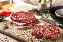 On a wooden cutting board on kraft paper there are raw beef burgers for burgers, spices, rosemary, a pepper mill, a. Cooking process. Top view. Still life. Copy Stock Image