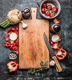 Wooden cutting board with organic vegetables and kitchen knife, healthy food background, top view Stock Photos