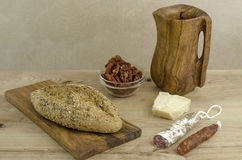 Wooden cutting board and pitcher and Bread, chorizo and olive Stock Images