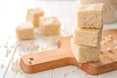 Wooden cutting board with rice treats. On white table Stock Images
