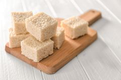 Wooden cutting board with rice treats. On white table Stock Photo