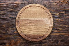 Wooden cutting board. Round wooden cutting board made of oak and ash, lies on a brown wooden table. space for text Royalty Free Stock Photography