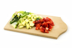 Wooden cutting board with various cut vegetables. Wooden cutting board with various vegetables isolated on white background Royalty Free Stock Image