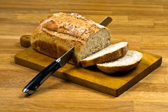 Wooden cutting board with white bread and knife Stock Photography