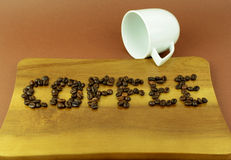 Wooden cutting board with word of coffee with coffee beans. On brown background Stock Photos