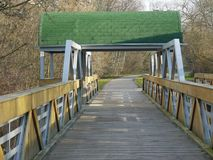 Wooden cycling bridge with green roof hood Stock Images