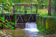 Wooden dam and small streem in autumnal forest. Royalty Free Stock Photos