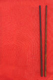 Wooden dark chopsticks on red. Fabric background Stock Photos