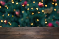 Wooden dark tabletop and blurred christmas tree bokeh. Xmas background for display your products. Wooden dark tabletop and blurred christmas tree bokeh. Xmas stock images