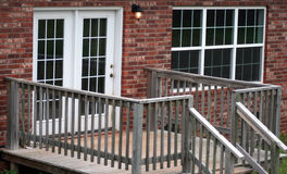 Wooden Deck. With stairway and railings around it in front of french doors on brick house or apartment Stock Photos