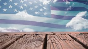 Wooden deck and American flag. Digital composite of a wooden deck with a view of an American flag waving stock footage