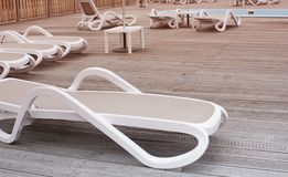 Wooden deck beach sea ocean resort sun lounger umbrella hotel pool sky sunrise. Relax by the sea on the wooden terrace sunset evening royalty free stock photos