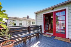 Wooden deck with a bench and red double door Stock Photos