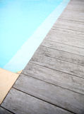 Wooden deck of blue swimming pool Stock Photography