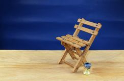 A wooden deck chair on a beach. A wooden deck chair as a symbol of vacation and relaxation on a blue background Stock Images