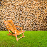 Wooden deck chair on green grass with stone wall Stock Image