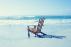 Wooden deck chair in the sand by the sea Royalty Free Stock Photography