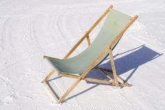 Wooden deck chair in snow Royalty Free Stock Photo