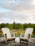Wooden deck with chairs and forest in background Stock Images