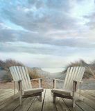 Wooden deck with chairs, sand dunes and ocean Royalty Free Stock Image