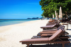 Wooden deck chairs on the sandy beach. Royalty Free Stock Photos