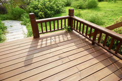 House wooden deck wood outdoor backyard patio in garden. Corner of empty wooden deck of house with balustrade in backyard garden. Outdoor backyard wood patio and