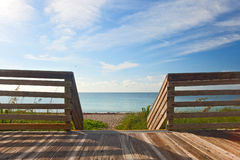 Wooden deck with fence overlooking the ocean and the beach Royalty Free Stock Photography