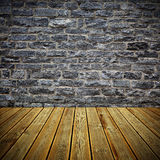 Wooden deck floor and brick wall. Striped wooden plank deck floor and grey stone slate wall stock image
