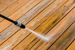 Wooden deck floor cleaning with high pressure water jet. Royalty Free Stock Photos