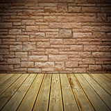 Wooden deck floor and stone bricks wall. Striped wooden plank floor and stone bricks wall royalty free stock photo