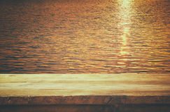 wooden deck in front of sea landscape at sunset Stock Photos
