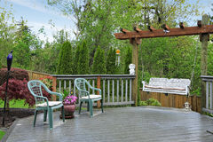 Wooden deck with garden swing Royalty Free Stock Image