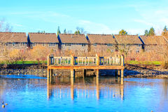 Wooden Deck by the Lake. A small wooden deck at the lake shore, with residence buildings in the back ground Royalty Free Stock Photography