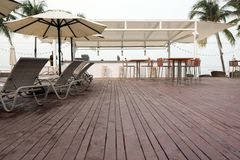 Lounge zone of tropical hotel. Wooden deck with lounge sunbeds and bar area on background of palms on tropical resort royalty free stock image