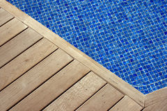 Wooden deck and mosaic pool. Details of wooden planking on a poolside deck with the blue mosaic pool bottom in the background royalty free stock images